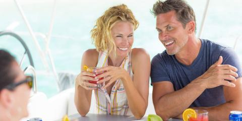 Happy couple drinking cocktails on a luxury crewed yacht