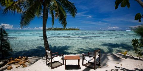 Chairs and table on empty beach in Tahiti