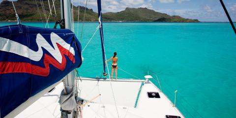 Woman on sailing catamaran trampoline