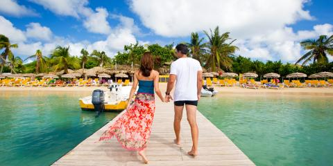 couple walking on dock toward beach