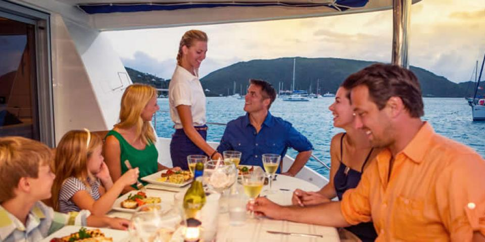 Hostess serving wine as a family sits down to a meal on a crewed yacht in the British Virgin Islands.