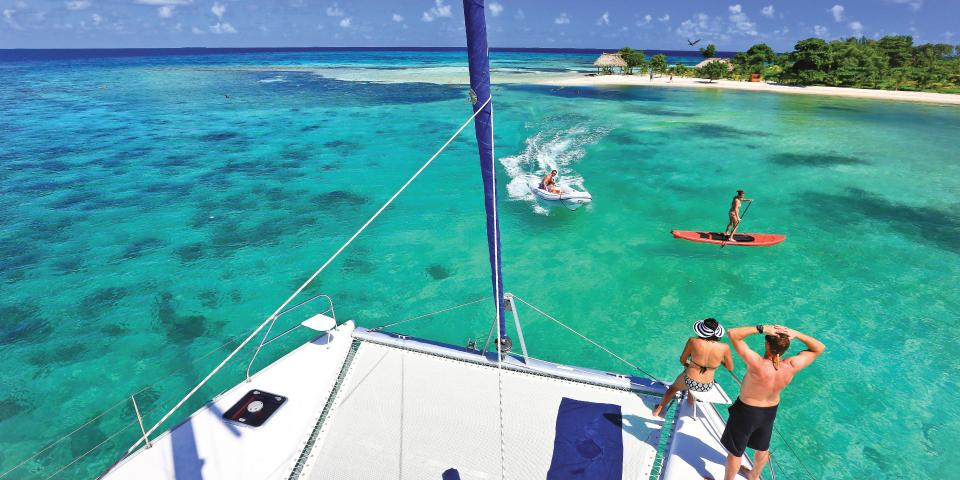 Stand up paddle boarder next to the catamaran in Belize