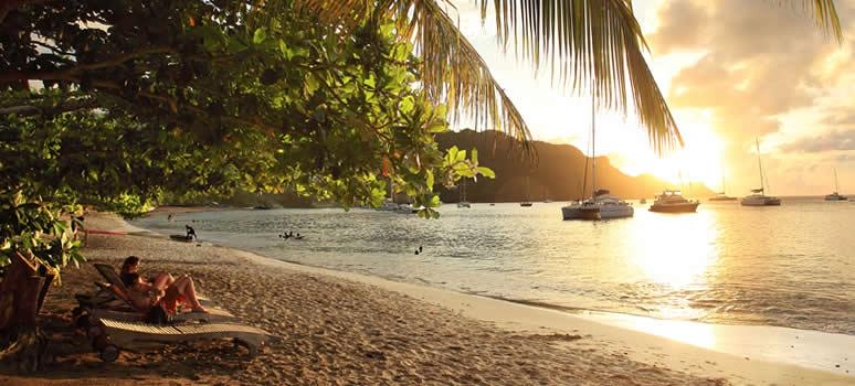 Sunset on a Beach in St. Lucia with boats in distance