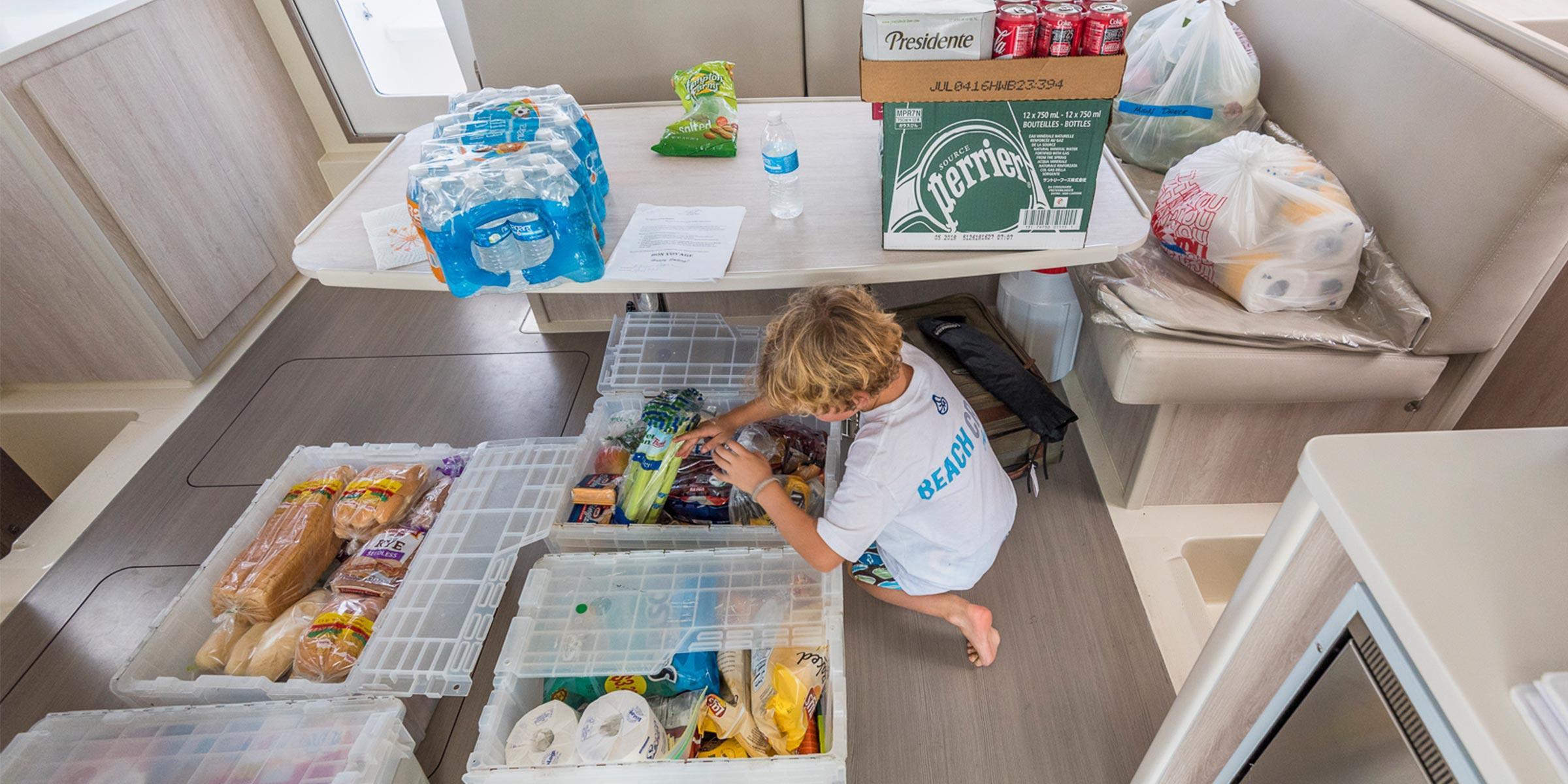 Boy unpacking provisioning on yacht