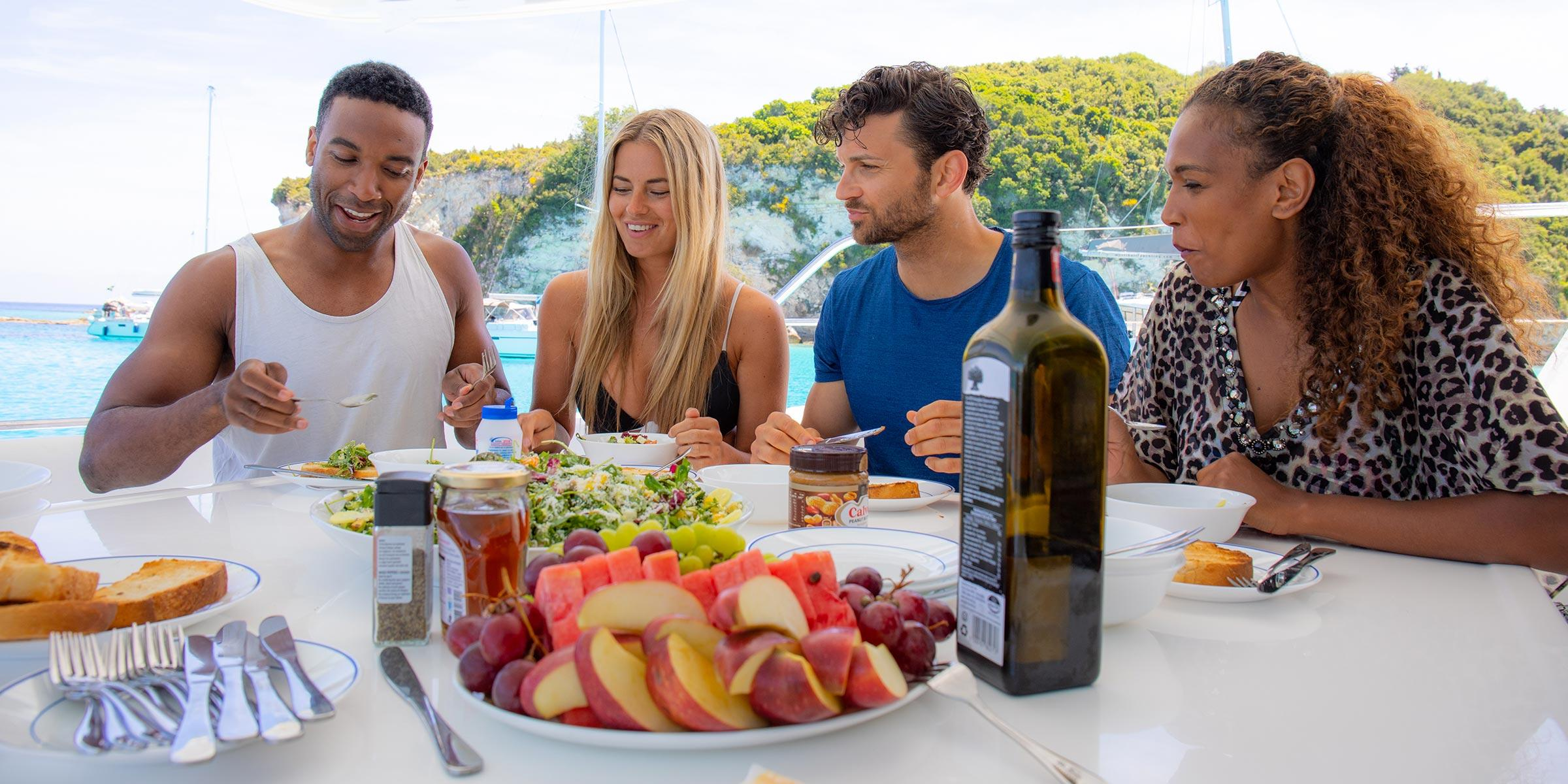 Friends at table on board yacht having lunch in Corfu