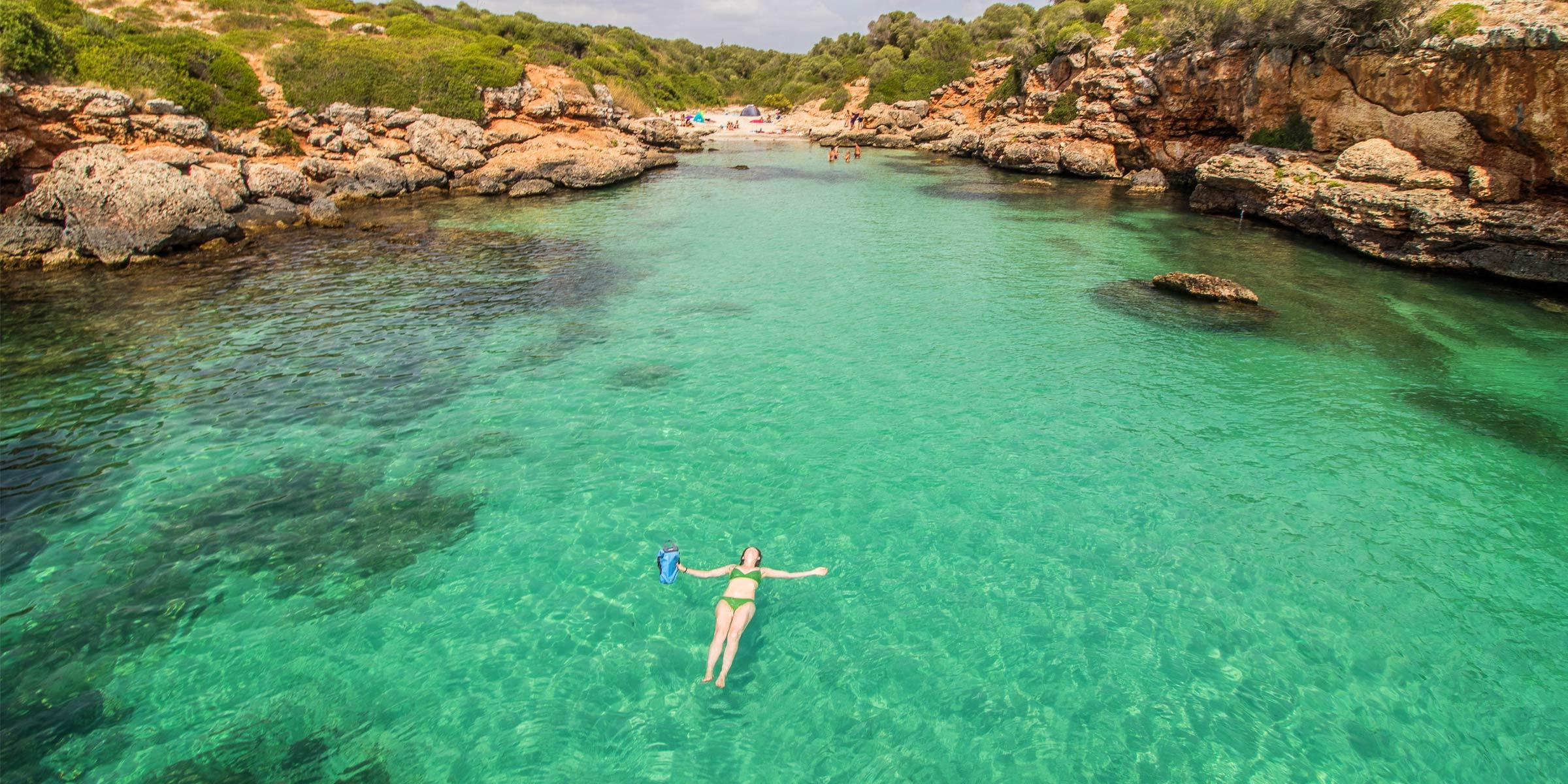 Woman swimming in a secluded bay on Mallorca Spain